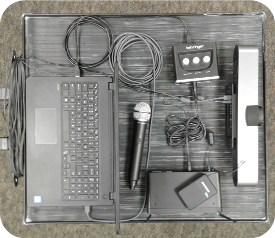 Image of cart style three. The Logitech camera is connected to the laptop via USB. A Samson 288 wireless base staion is shown with its two mics. The 288 base is connected from its unbalanced, mixed output to the Behringer UM2 audio interface via a mono, tip-ring-sleeve cable. The cable is plugged into the mic-1 input on the UM2 interface. The interface is then connected via USB to the laptop.